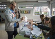 Elettore che presenta busta dentro l'urna al collegio elettorale per le elezioni generali spagnole a Madrid, Spagna Immagini Stock