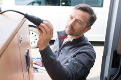 Elettricista automobilistico bello che installa presa a muro in campeggiatore fotografie stock