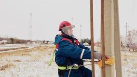 Elettricista in casco elevato alla linea elettrica facendo uso della cinghia al palo archivi video