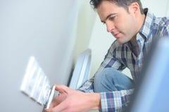 Elettricista che aggiunge l'incavo elettrico dell'aggiunta sulla parete immagine stock