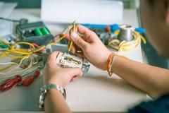 Elettricista che installa zoccolo chiuda su di spirito delle mani dell'elettricista immagine stock
