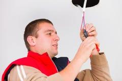 Elettricista che lavora con i cavi ed altri utensili Fotografia Stock