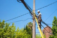 Elettricista che ripara i cavi sul palo della rete della città dentro Immagini Stock
