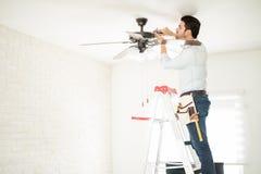Elettricista che ripara un ventilatore da soffitto fotografia stock libera da diritti