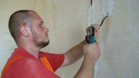 Elettricista con le pinze che puliscono i cavi in scatola di giunzione per l'incavo stock footage