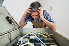Elettricista confuso che esamina il contenitore di fusibile Fotografie Stock