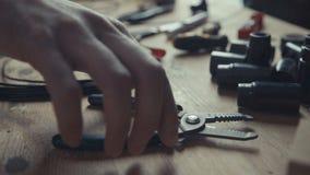 Elettricista dell'artigiano che lavora ai collegamenti facendo uso delle paia delle pinze per spogliare Fotografia Stock
