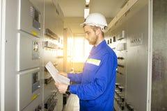 Elettricista Engineer sul pannello di controllo con lo schema elettrico Manutenzione dei materiali elettrici fotografie stock