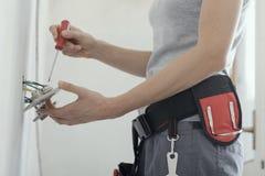 Elettricista femminile che ripara un incavo a casa immagini stock libere da diritti
