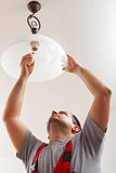 Elettricista finito montando la lampada del soffitto Fotografie Stock Libere da Diritti