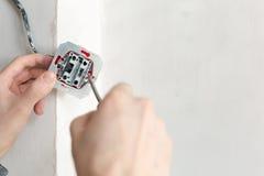 Elettricista Hands With Screwdriver che installa presa a muro fotografia stock libera da diritti