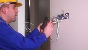 Elettricista maschio che controlla sbocco con l'attrezzatura speciale Uomo con il casco video d archivio