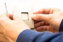 Elettricista maschio che mette copertura sul commutatore elettrico Fotografie Stock Libere da Diritti