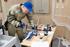 Elettricista matrice che sega la scatola di plastica per la stenditura dei cavi Immagini Stock Libere da Diritti