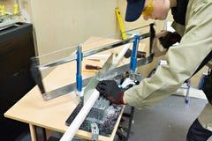 Elettricista matrice che sega la scatola di plastica per la stenditura dei cavi Fotografia Stock