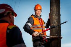 Elettricista su un palo contro il cielo blu Fotografie Stock Libere da Diritti