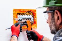 Elettricista sul lavoro su un pannello elettrico fotografie stock