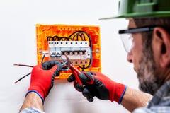 Elettricista sul lavoro su un pannello elettrico fotografia stock