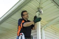 Elettricista Taking Glass Cover fuori dalla lampada dell'esterno Fotografie Stock