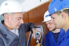 Elettricisti che installano le plafoniere in costruzione immagini stock