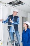 Elettricisti che installano le plafoniere nella casa domestica fotografia stock