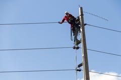 Elettricisti che lavorano ad un pilone immagine stock