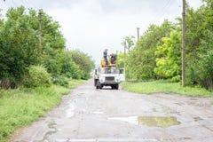 Elettricisti che lavorano ai pali, a fotografia stock