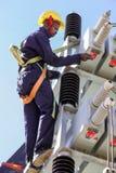 Elettricisti che lavorano alle linee elettriche ad alta tensione immagine stock