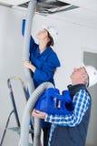 Elettricisti che misura i tubi flessibili di CA nel soffitto delle costruzioni fotografie stock libere da diritti