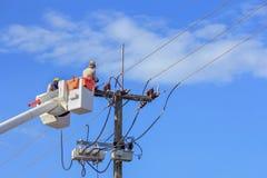 Elettricisti che riparano cavo della linea elettrica sul palo di energia elettrica Immagine Stock