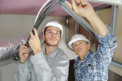 Elettricisti del figlio e del padre che lavorano al soffitto delle costruzioni fotografie stock