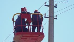 Elettricisti sul cambiamento della torre i cavi sul primo piano elettrico di sostegni video d archivio