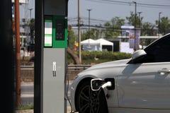 Elettricità di rifornimento di carburante bianca dell'automobile elettrica della berlina ai grafici elettrici per le automobili fotografie stock