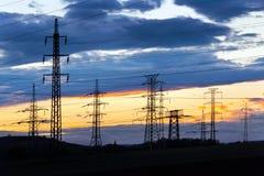 Elettricità - industria energetica di potere - pali elettrici ai soli fotografie stock libere da diritti