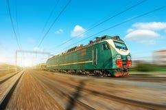 Elettrico locomotivo con un treno merci ai giri ad alta velocità dalla strada di ferrovia Fotografie Stock Libere da Diritti
