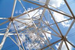 Elettrodotti di vista dal basso contro cielo blu Immagini Stock