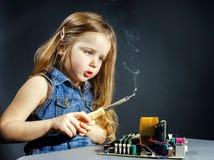 Elettronica sveglia di riparazione della bambina dal bottaio-pezzo Fotografie Stock Libere da Diritti