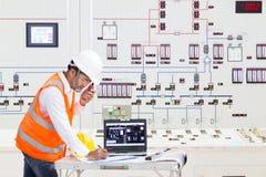 Elettrotecnico che lavora alla sala di controllo della centrale elettrica termica immagini stock