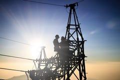 Elettrotecnico dell'uomo di Silhouetteblack e lavoratori elettrotecnici Fotografia Stock Libera da Diritti