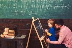 Elev med läraren på skolan Fader och son för sidosikt att lära aritmetisk Pappa som förklarar likställande till den gulliga ungen arkivfoto