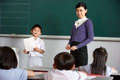 Elev och lärare vid Blackboard I kinesgrupp Arkivfoto