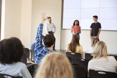 Elev som frågar fråga under presentation av högstadiumstudenter royaltyfria bilder