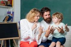 Elev som lär bokstäver och nummer - matematikbegrepp Unga par som hjälper hans son att göra läxa l?ra och arkivbilder