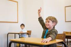 Elev som lyfter hans hand på hans skrivbord Arkivfoto