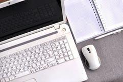 Elevação acima da vista do local de trabalho do escritório com fim do portátil acima do teclado e do rato de computador com cader Foto de Stock
