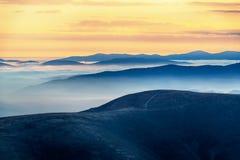 Elevação maravilhosa da manhã nas montanhas com as nuvens abaixo do mo imagem de stock