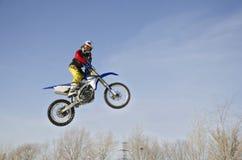 Elevação no piloto do MX do ar em uma motocicleta, em um fundo nebuloso Fotos de Stock Royalty Free