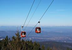 Elevación de esquí del teleférico sobre paisaje de la montaña imagenes de archivo