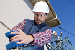 Elevación de funcionamiento del cielo del trabajador para hacer el trabajo de mantenimiento al aire libre fotos de archivo libres de regalías
