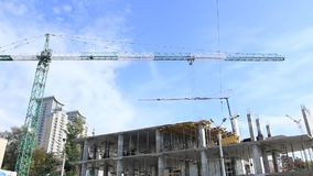 Elevación de la grúa de construcción contra el cielo azul metrajes